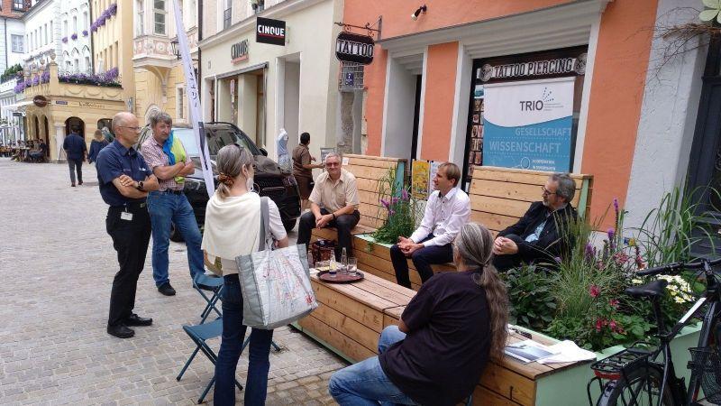 Das Bild zeigt Menschen um eine Bank im Gespräch.